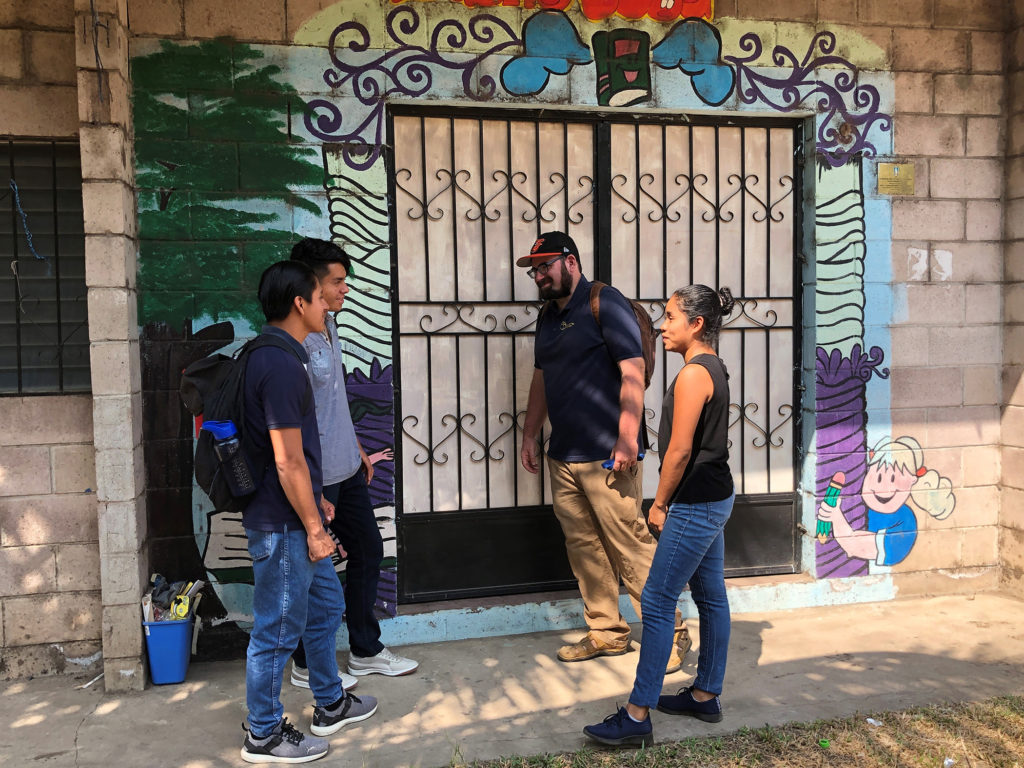 (From left) César Hernández, William Mendez, Larry Parr and Yadira Quilzapa wait outside the community library in Las Delicias.