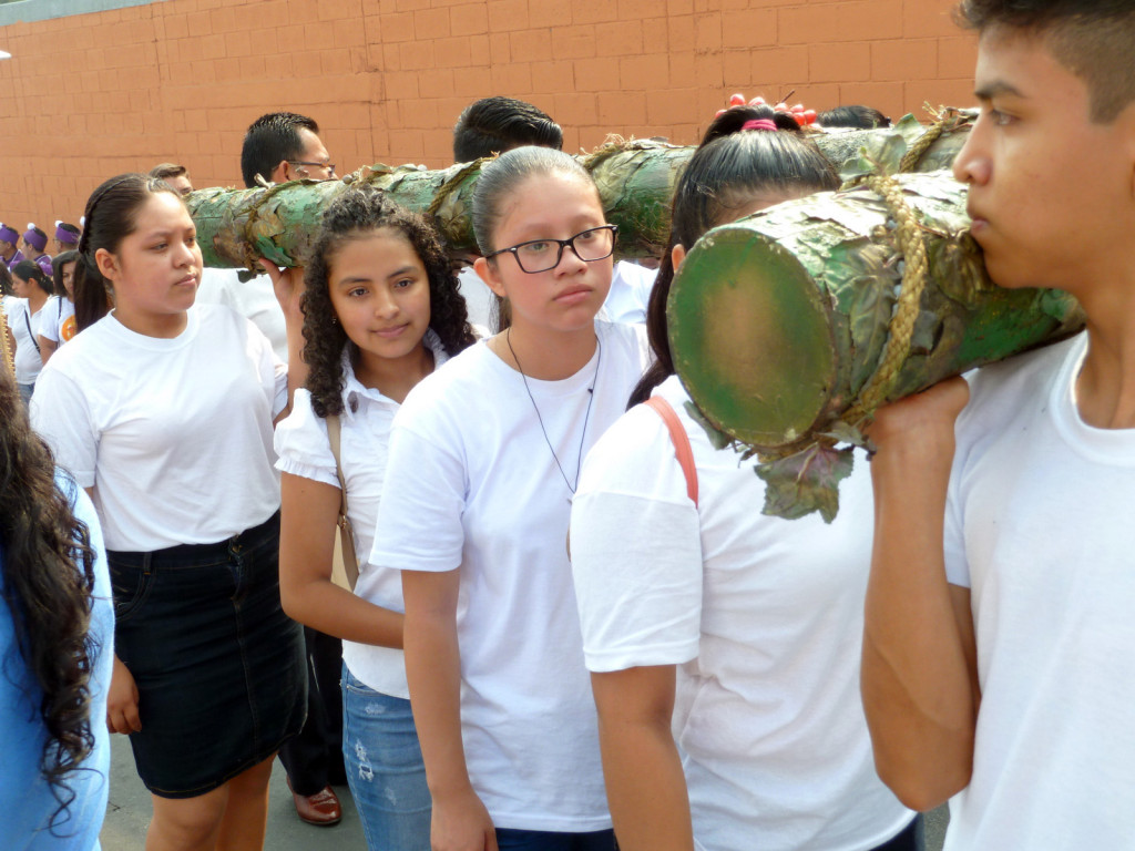 A dozen youth carry a giant wooden cross during the Good Friday procession in Cojutepeque. The cross they carry is heavy, but people step up to help bear it.