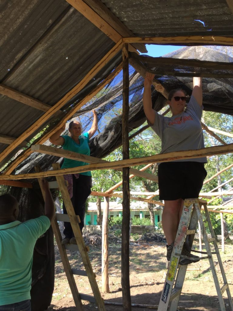 Sami Scott (left) and Abby Belt set up a new cover at the tree nursery of the Jean Marie Vincent Agricultural Center in Gros Morne, Haiti, to provide shelter for tree saplings.